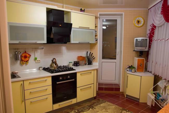 Угловая желтая кухня с выходом на балкон (14 фото)