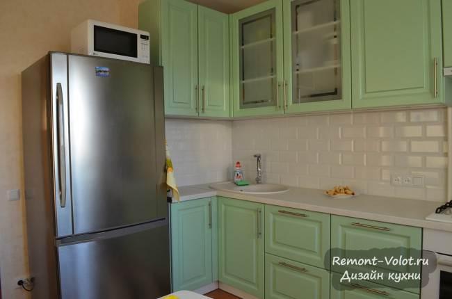 Серебристый холодильник на светло-зеленой кухне