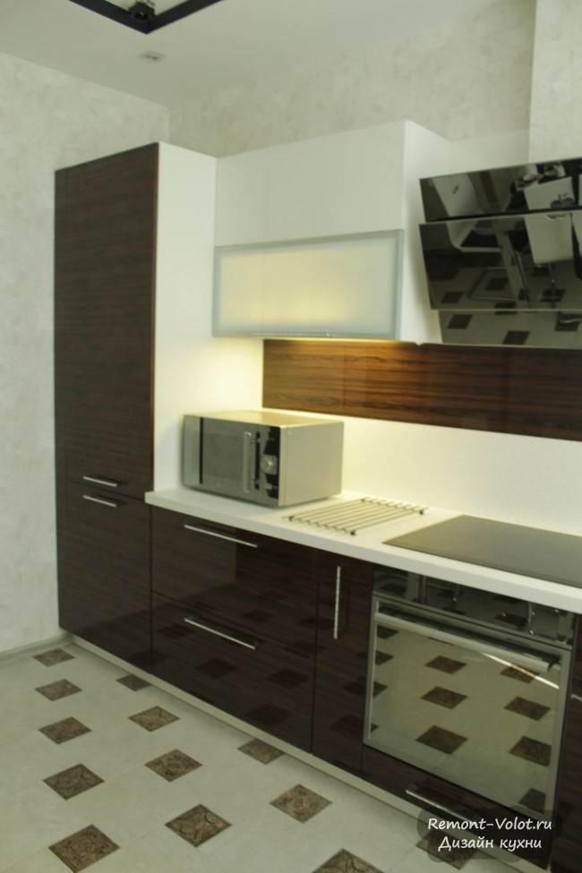 Встроенный холодильник скрывают фасады кухни с текстурой дерева