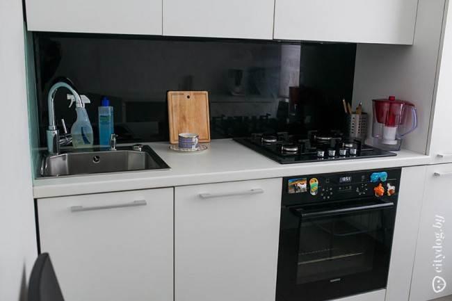 Черный стеклянный фартук на прямой белой кухне