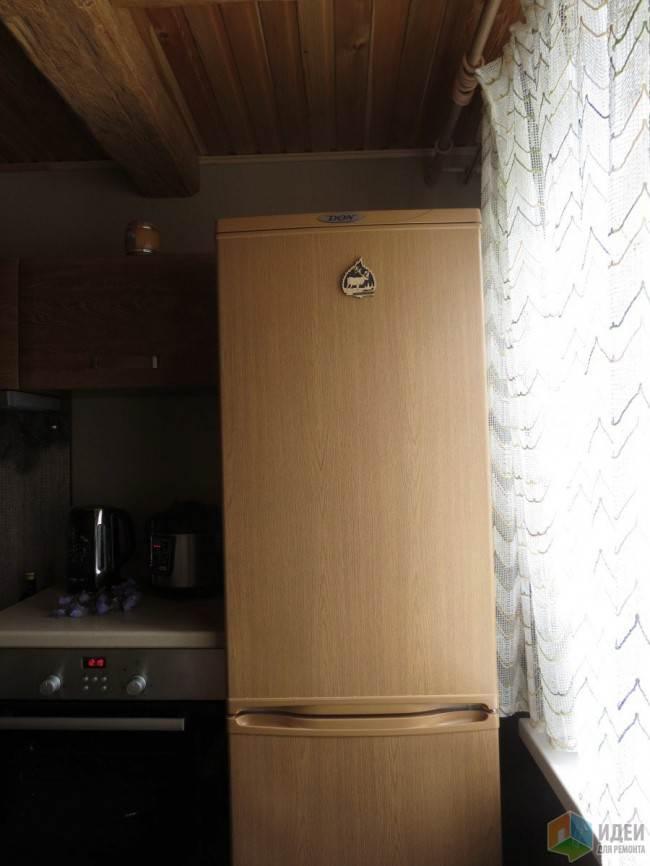Отдельностоящий холодильник на угловой кухне под дерево