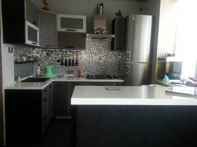 Угловая современная кухня под дерево с фартуком из мозайки под металл