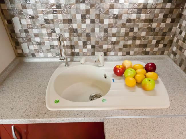 Белая мойка Blanco на красно-белой угловой кухне