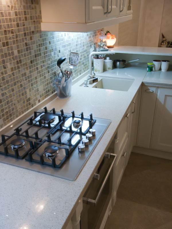 Светло-коричневая столешница из камня на угловой кухне