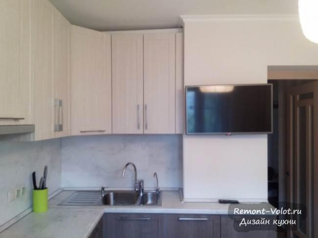 Угловая кухня под дерево с телевизором на стене