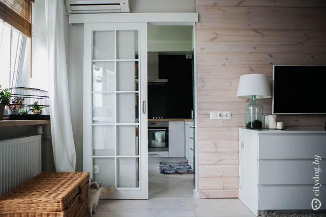 Белая раздвижная дверь лаконичной формы на кухне
