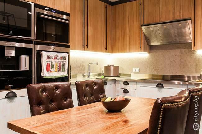 Дизайн угловой кухни с фасадами под дерево и обеденной зоной на 33,6 кв. м