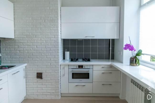 Угловой гарнитур белого цвета разделяет стена, облицованная искусственным камнем
