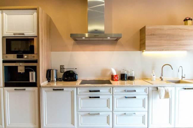 Неоклассическая прямая кухня из белого массива в комнате, совмещенной с гостиной