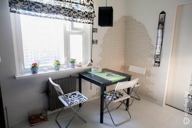 Черно-белая обеденная зона и стены кухни, облицованные искусственным камнем