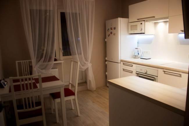 Дизайн белой кухни 10,7 кв. м с выходом на балкон