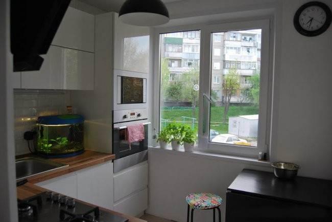 Белая кухня с деревянной столешницей и высоким пеналом для техники