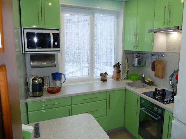Зеленая кухня в хрущевке с рабочей поверхностью вдоль окна