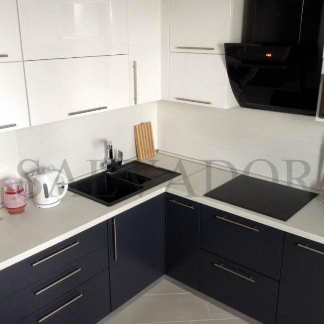 Угловая бело-серая кухня с черной каменной мойкой