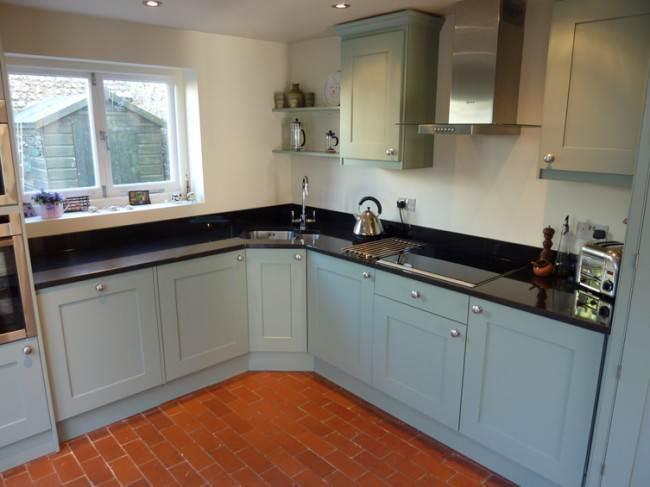 Угловая кухня со стиральной машиной, посудомойкой, морозильной и холодильной камерой, которые встроены в нижние модули