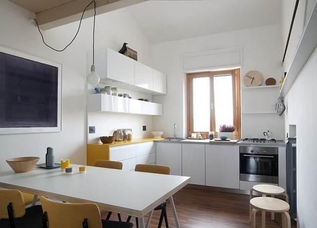 Мойка и рабочая поверхность возле окна на угловой кухне