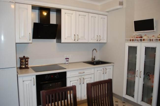 Белая классическая кухня ЗОВ 10 кв.м с обеденной зоной и телевизором