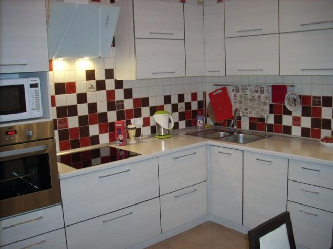 Угловая белая кухня с ярким фартуком