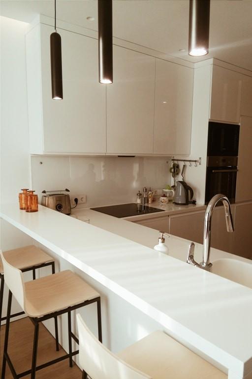 Современная белая кухня без ручек. Барная стойка с интегрированной мойкой