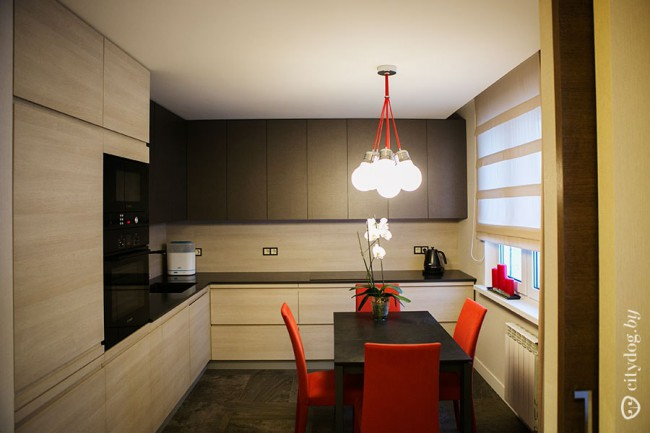 Современная кухня со встроенной техникой и красными стульями