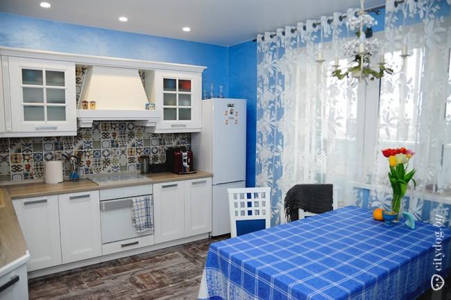 Дизайн белой кухни 12 кв.м с голубыми стенами и яркой плиткой на фартуке