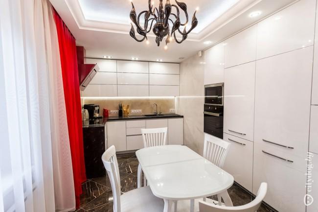 Дизайн белой кухни 12 м с красными шторами и вытяжкой