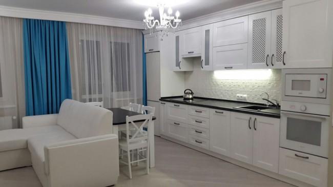 Интерьер белой кухни-гостиной 20 кв.м с черной столешницей и бирюзовыми шторами