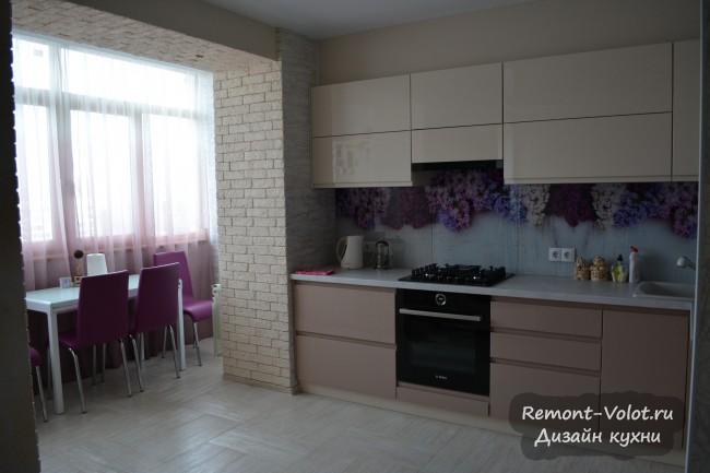 Бежевая кухня с фартуком с сиренью, совмещенная с балконом и гостиной