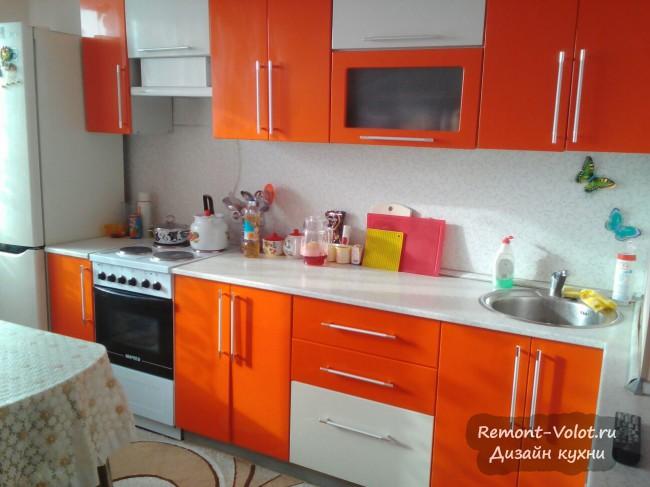 Оранжевая кухня 12 кв. м с телевизором и диваном