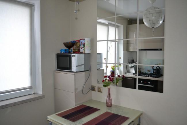Дизайн 6-метровой кухни с глянцевыми фасадами и зеркалом над столом