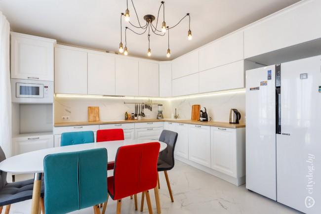 Дизайн белой кухни 15 кв м с деревянной столешницей и яркими стульями