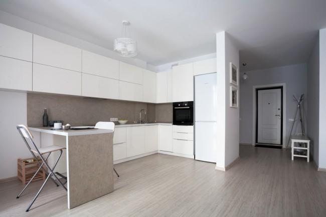 Современная белая кухня с фасадами без ручек в квартире-студии