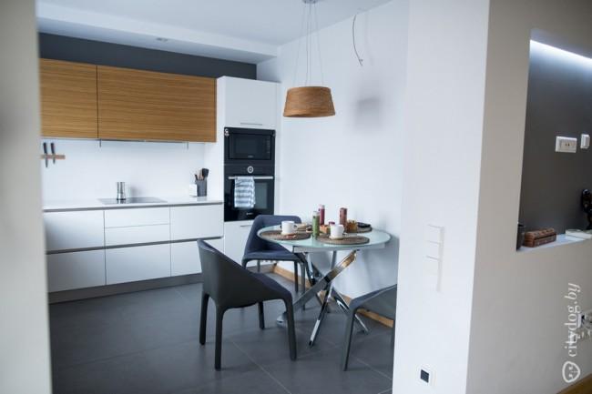 Белая с деревом угловая кухня 12 кв без ручек с выходом в гостиную