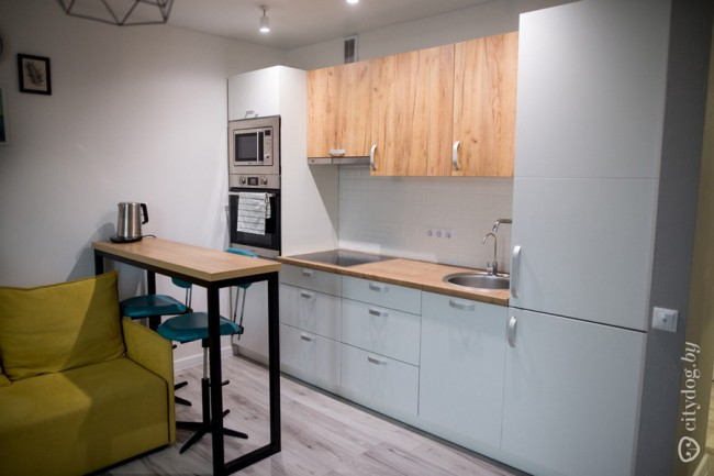 Дизайн кухни 12 кв м в скандинавском стиле с желтым диваном и выходом на балкон
